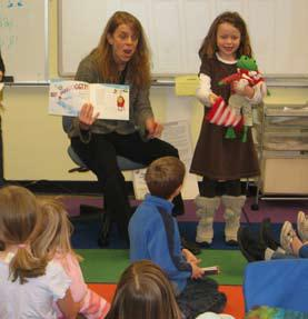 Teacher reads to class while student holds props for the story